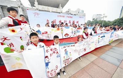 """图为小学生们在展示""""文明出行在滁州""""百米绘画作品.-少儿绘画倡"""